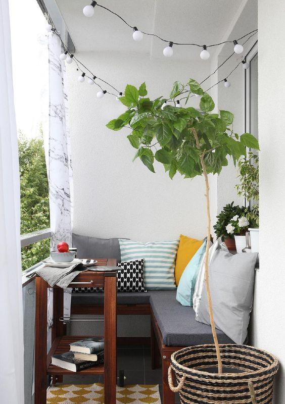 a small cozy balcony with an L-shaped upholstered bench, a small coffee table and potted plants