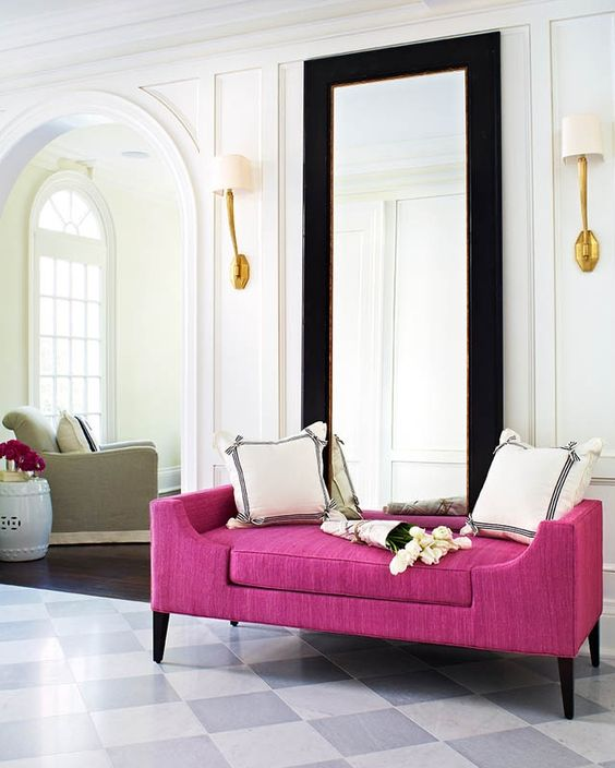 a very elegant entryway with a bright magenta bench, which adds cheer and color