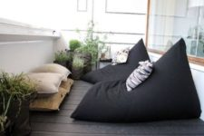 22 a Scandinavian balcony with blackbean bag chairs and neutral pillows plus potted greenery