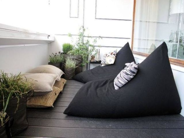 a Scandinavian balcony with blackbean bag chairs and neutral pillows plus potted greenery