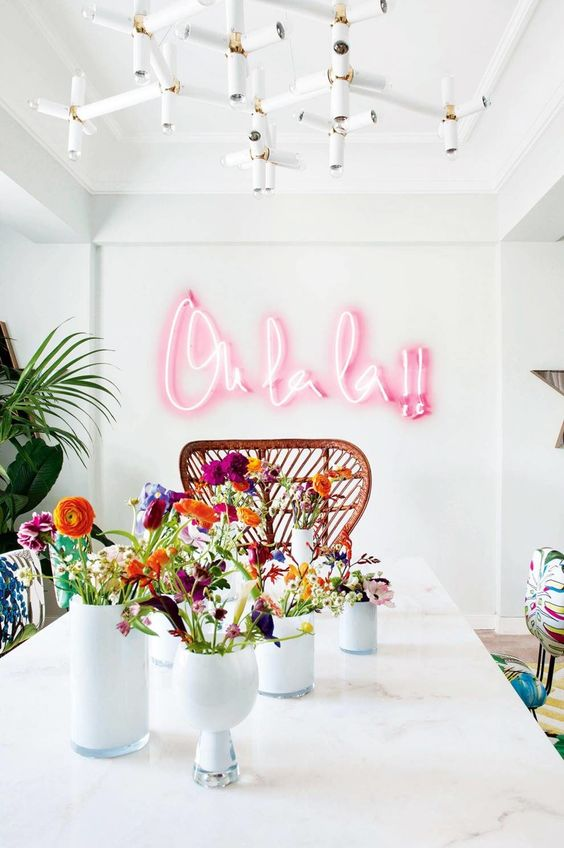 a bright dining space spruced up with tropical touches and a pink neon light word for fun