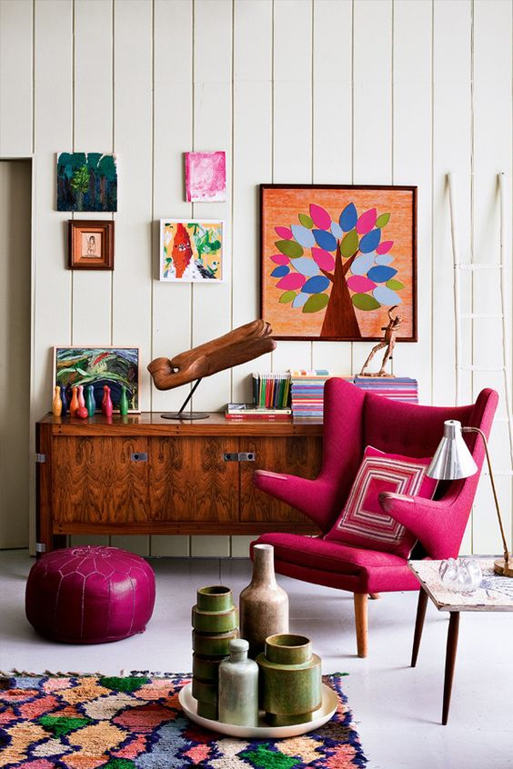 a bright mid-century modern space with a magenta chair and ottoman plus bright artworks