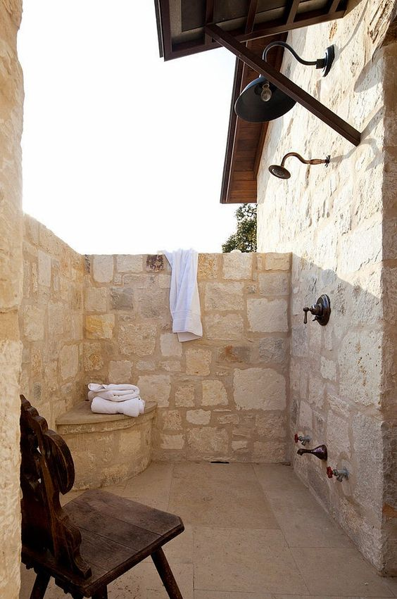 a cozy outdoor rustic shower fully clad with stone, with a little built-in storage item and a chair