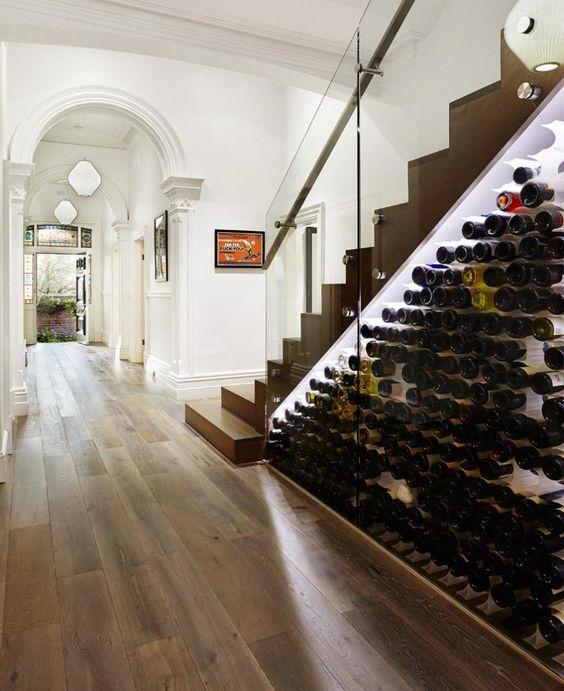 a modern wine storage space under the stairs with lots of bottles and additional lights to see them all