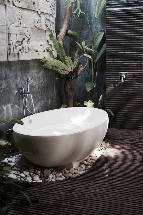 a spa-like outdoor space with a dark stained deck, cutout art on the wall, pebbles and an oval bathtub