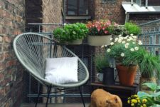 22 a summer balcony with potted greenery and blooms, a chair, a rug and candles