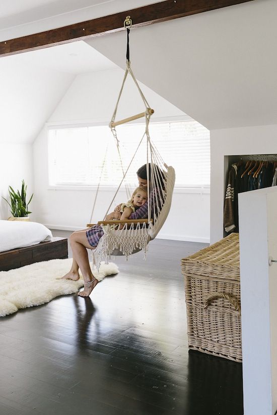 a laconic bedroom with a boho feel and relaxed vibes expressed by a hammock  chair and a wicker chest