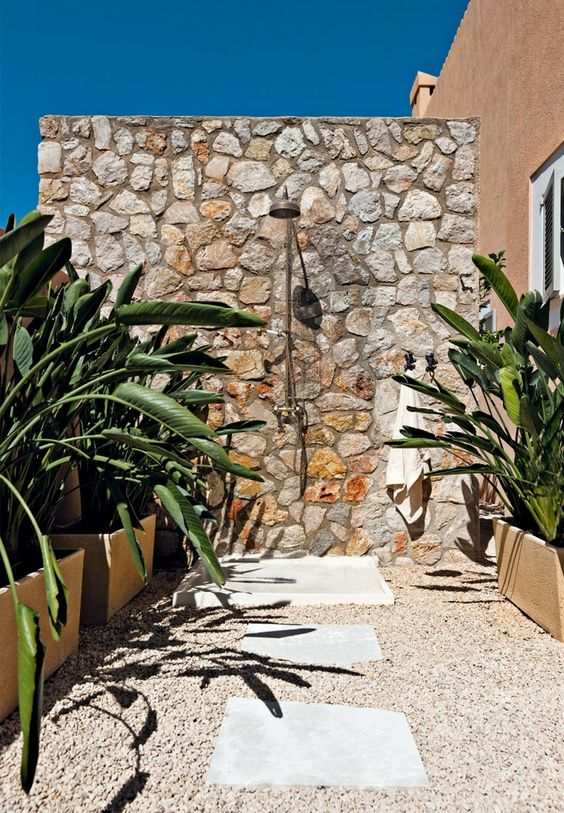 a lovely outdoor shower with a stone wall, pebble and stone floor and potted plants