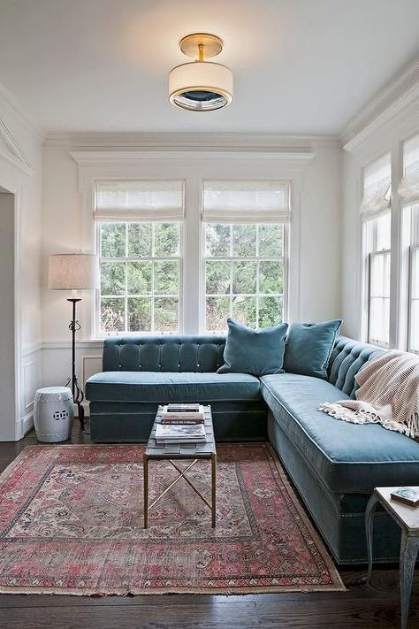 a mid-century modern space with a large muted blue velvet banquette seating