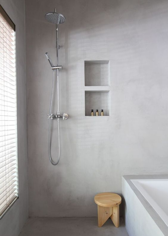 a minimalist bathroom with light grey plaster walls and floor looks very peaceful and welcoming