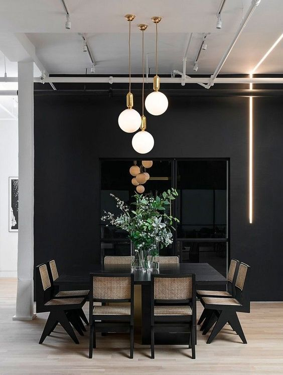 a moody dining space done with a cluster of pendant lamps and a neon tube light to make it more contemporary