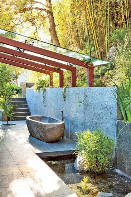 a tranquil outdoor oasis with a stone wall, a little pond and a stone carved bathtub
