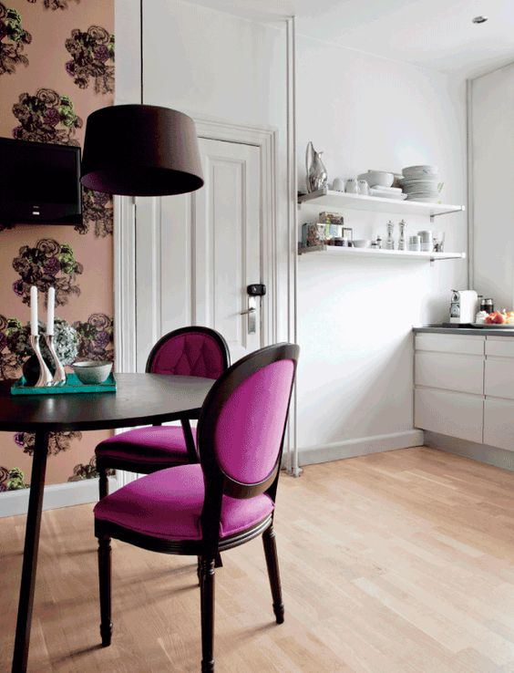 a chic dining space with elegant magenta chairs and floral wallpaper to separate it from the kitchen
