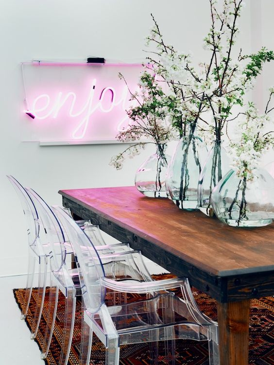 a modern dining space done with a pink neon light and acrylich chairs that contrast the wooden table