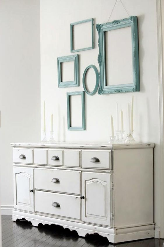 a neutral shabby chic space is injected with color using aqua-painted frames on the wall