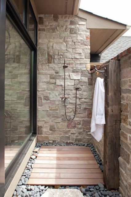 a small yet stylish outdoor shower clad with stone and bricks, a wooden deck and pebbles on the ground