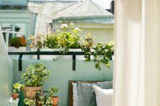 24 a very small balcony with a wooden crate as a table, an upholstered bench, a ladder and lots of potted greenery