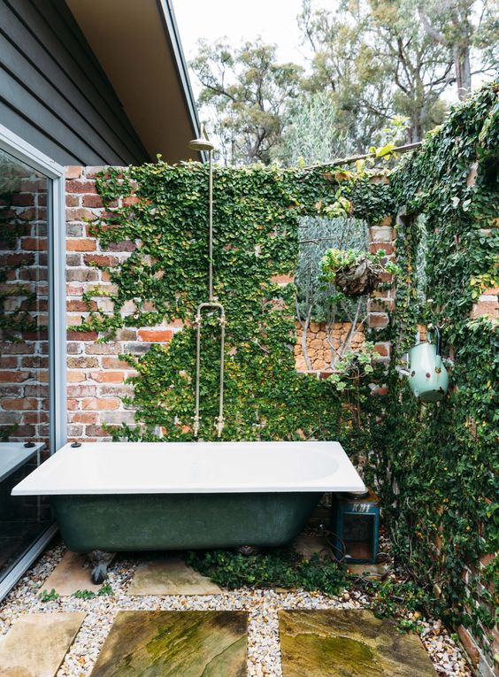 a vintage industrial outdoor space with a brick wall covered with winves and a green bathtub