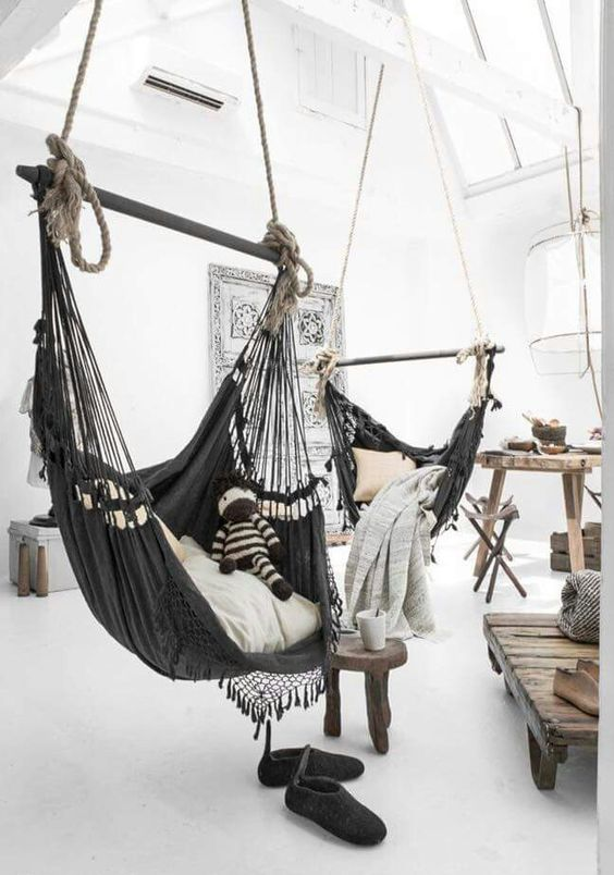 a wabi-sabi interior with a couple of dark hammock chairs instead of usual sitting furniture