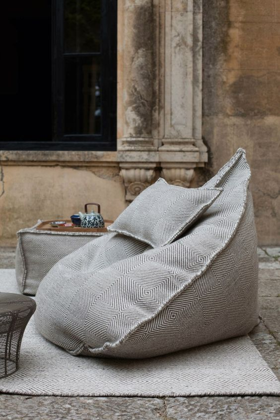 grey printed bean bag chairs and ottomans plus a rug to create a comfortable outdoor space