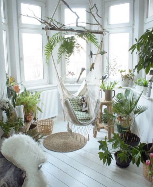 an awkward nook filled with potted greenery and a hammock chair is a great idea to use dead space