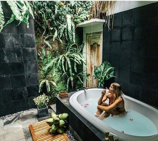 an outdoor sanctuary with a tile clad bathtub, pebbles and a wooden mat plus potted plants