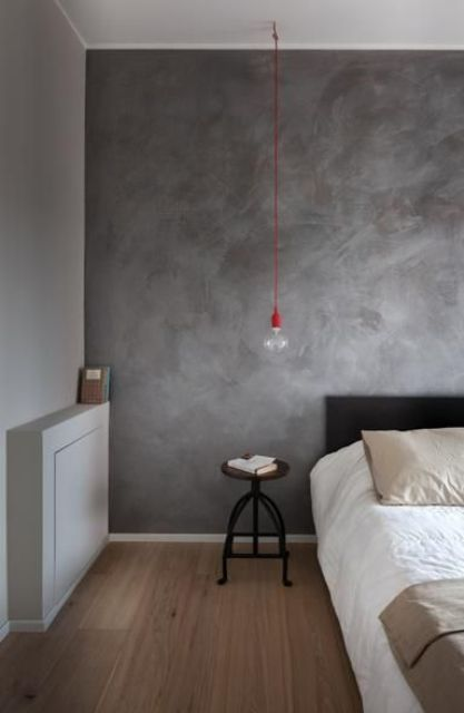 spruce up your simple industrial bedroom with a dark grey plaster wall behind the headboard