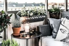 26 lots of pots with greenery, a wicker chair, a coffee table and a large candle lantern for coziness