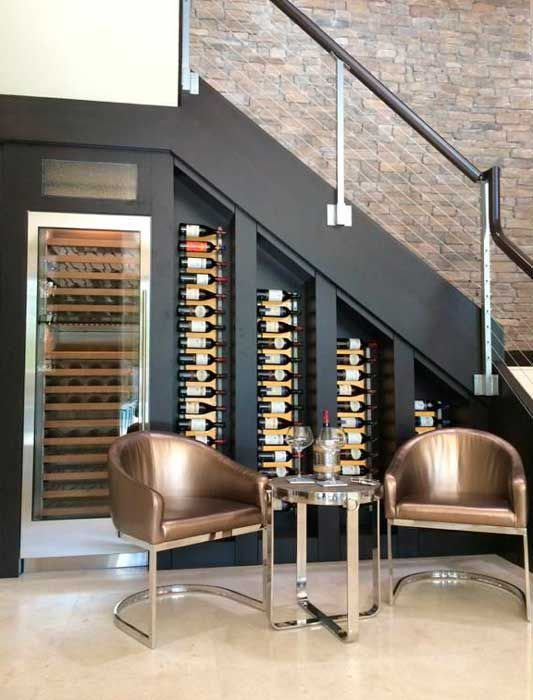 wine bottles on wall mounted shelves and a special cooler plus a sitting space to have a drink here
