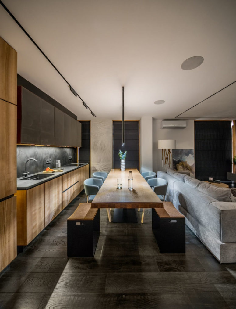 The kitchen and dining space are done in light-colored wood and dark greys for a contrast
