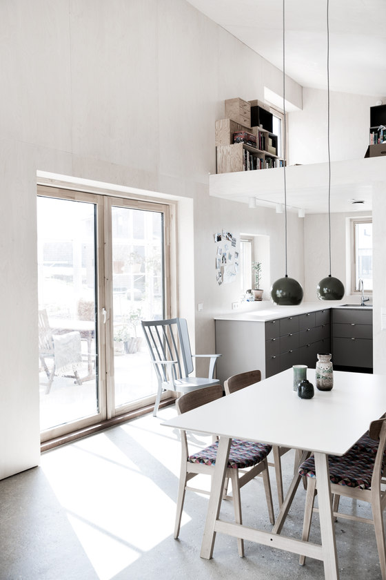 The kitchen and dining spaces are united in the open layout, there are grey cabinets and chairs with colorful cushions