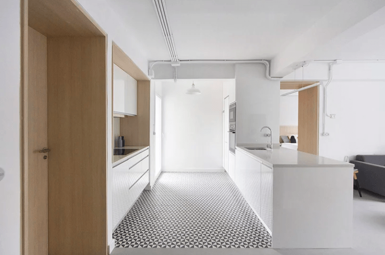 The kitchen is done with sleek white cabinets, a geometric floor and light-colored wood surfaces