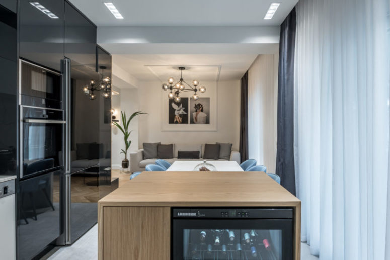 The kitchen, living and dining rooms became one open layout separated only with a large kitchen island of wood and marble