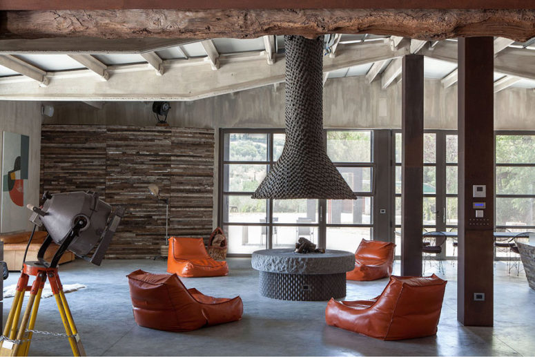 The main layout includes a living and dining space plus a kitchen, it's done with concrete, weathered wood and metal, a large hearth with orange chairs is a centerpiece