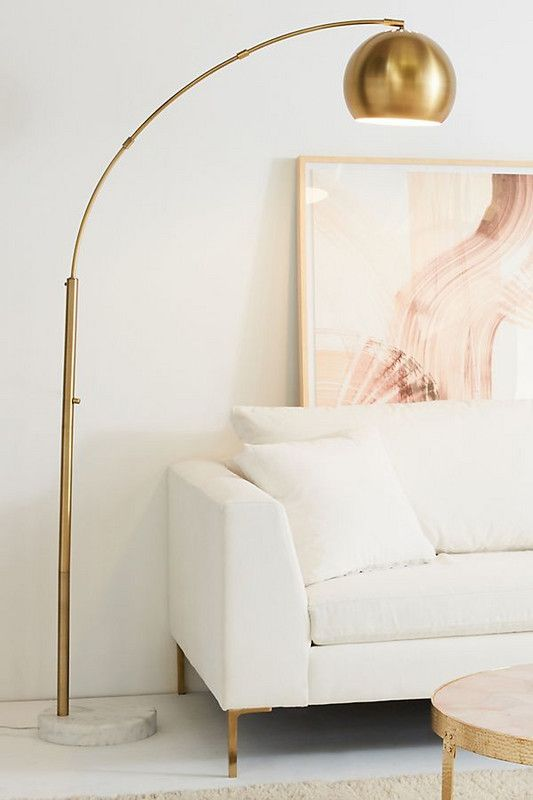 a brass arc lamp with a marble base is a chic and glam toouch that will fit many decor styles