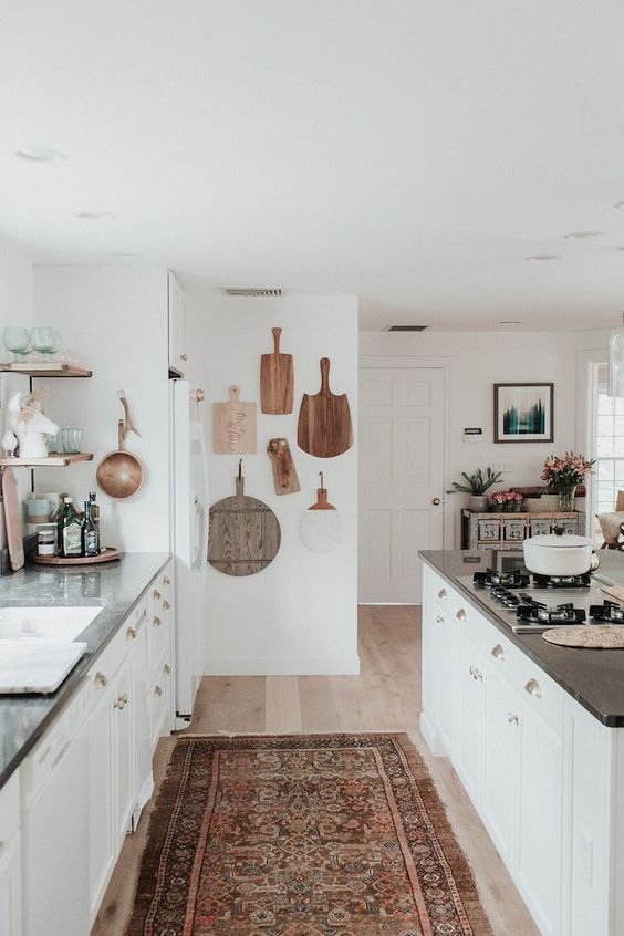 a coastal meets boho kitchen with a vintage boho rug, boards on the wall and neutral furniture