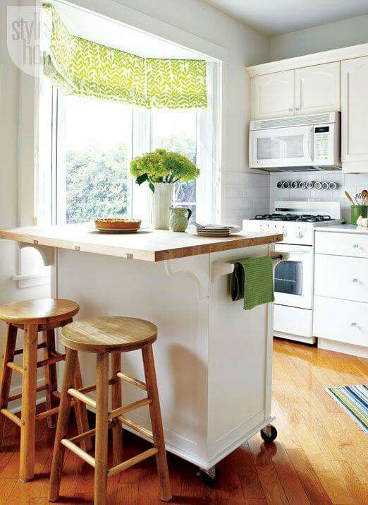 a mobile white kitchen island with a wooden countertop and much storage plus an eating space