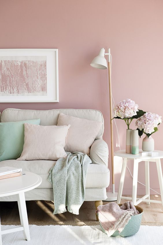 a pastel living room with much neutrals, pink and some mint-colored accents