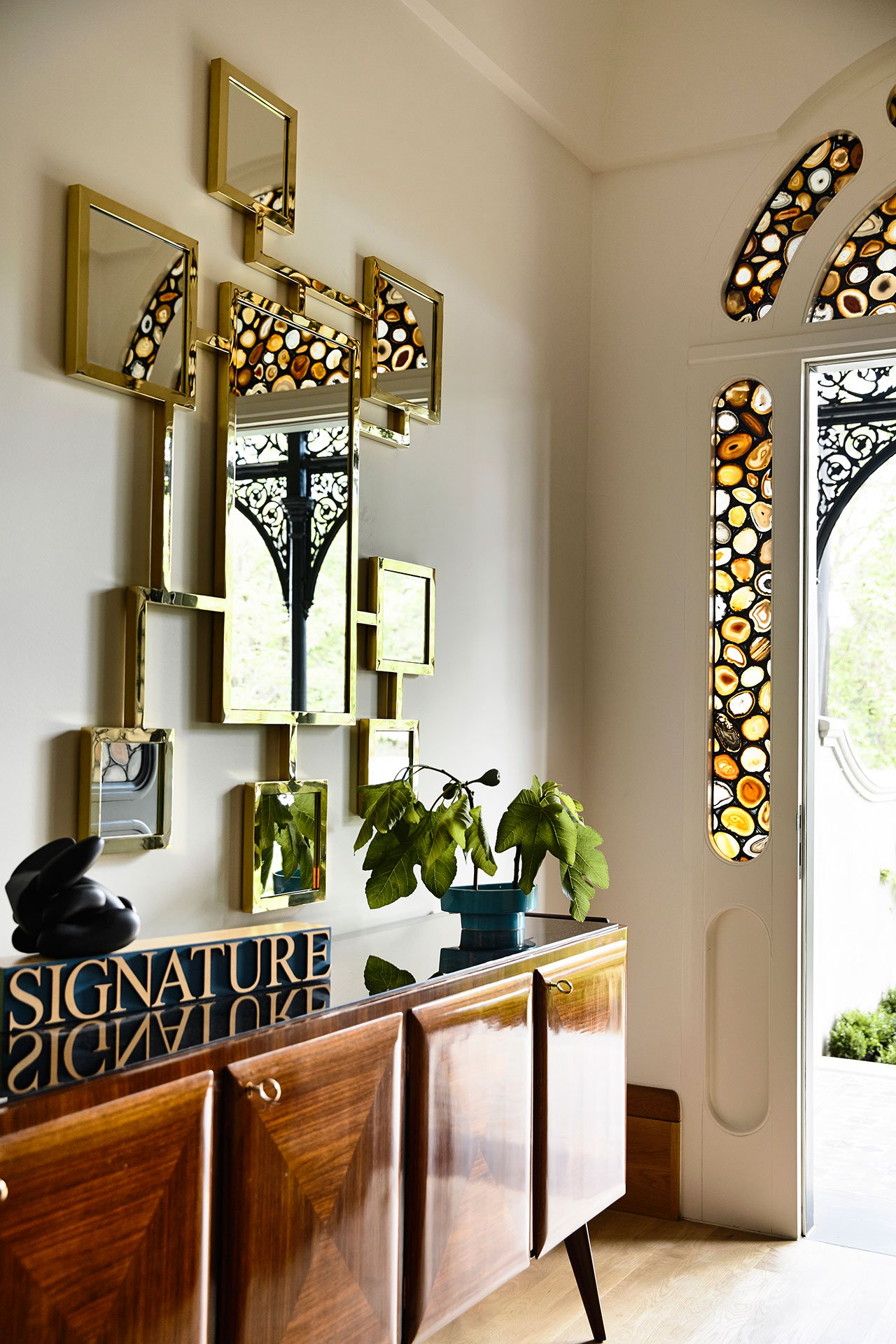 The entryway is done with art deco mirrors and furniture and mosaic glass