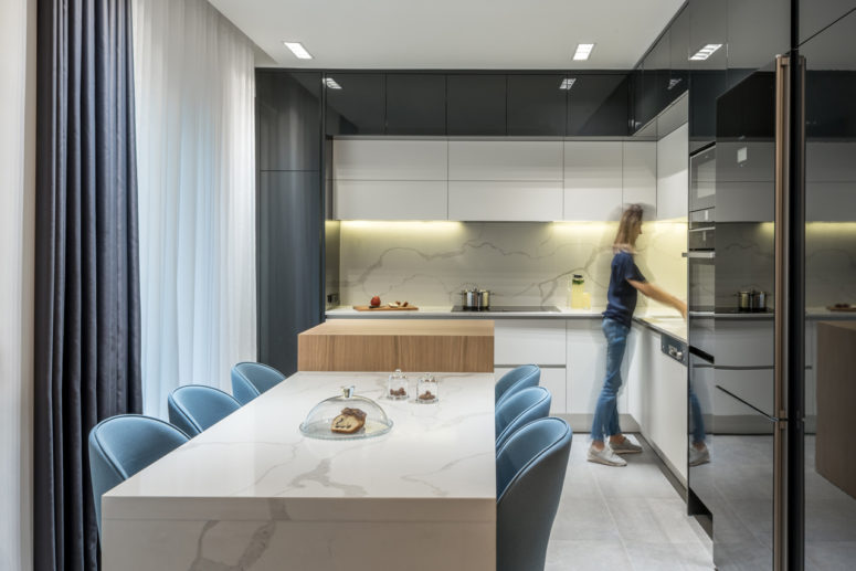 The kitchen is black and white, with a white marble backsplash and lights and a cooking surface of wood