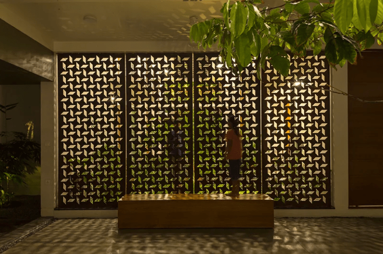 The perforated facade casts patterns across the home's interior