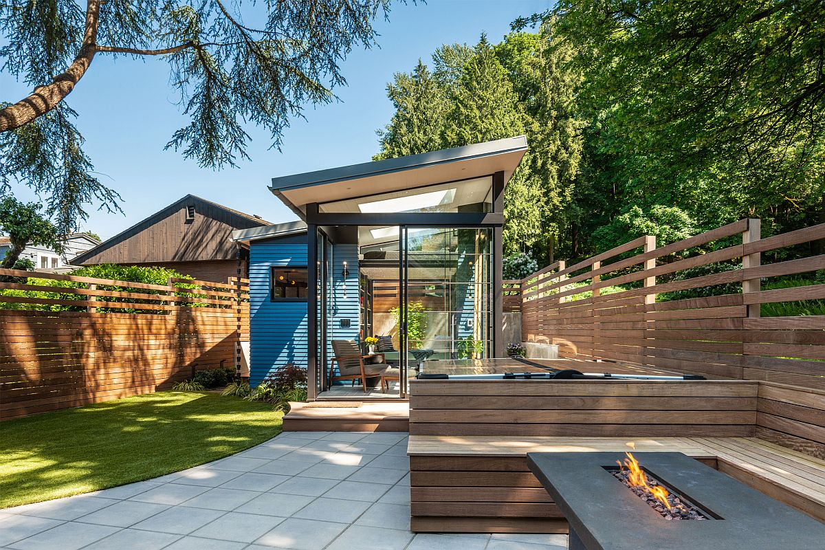 The shed is clad with glass and wood and is opened to the backyard