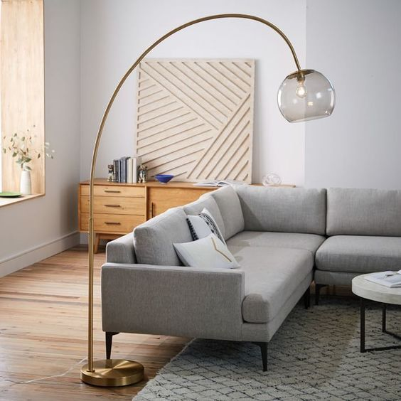 a brass curved floor lamp with a smoked glass lampshade will add a refined touch to your space