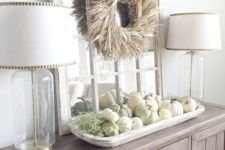 03 a farmhouse buffet with a corn husk wreath over the table and a tray with white and green pumpkins plus moss