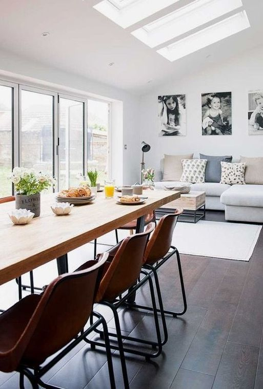 a gallery wall of personal family black and white pics is the focal point in this open layout
