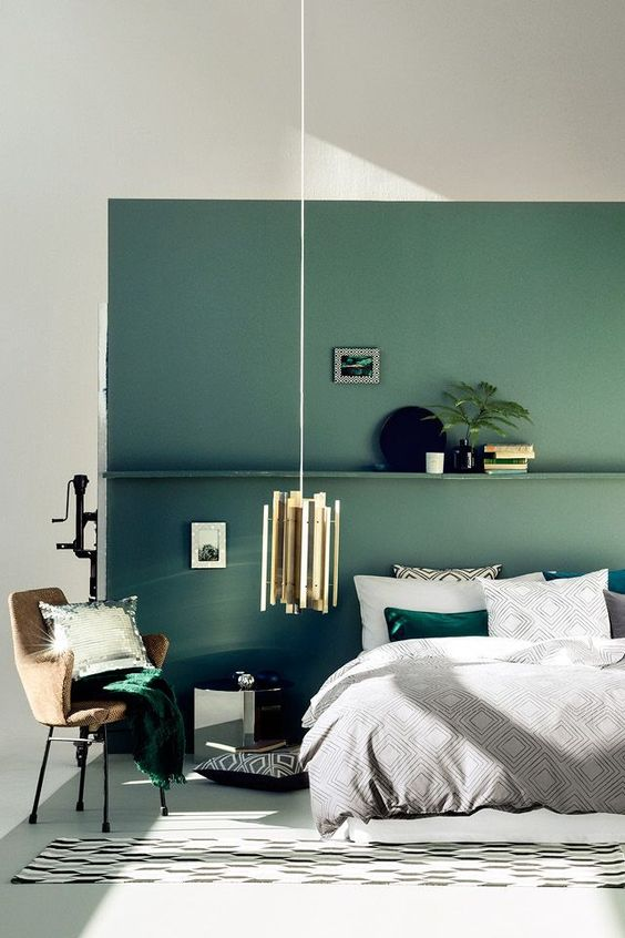 a muted green accent wall with a shelf and matching emerald bedding and a pillow