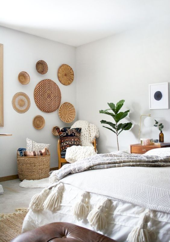 some wicker baskets on the wall, a basket for storage, tassels and chunky knit for a boho bedroom