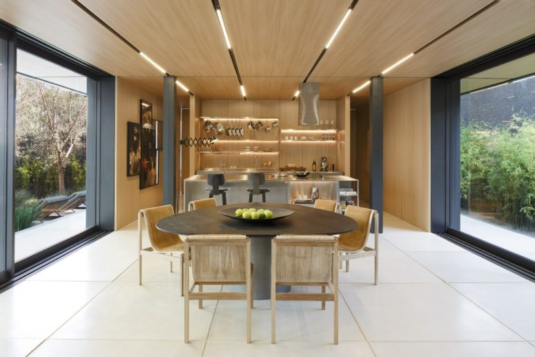 The dining space is united with the kitchen, there's much wood and metal pillars, the space can be opened to outdoors on two sides
