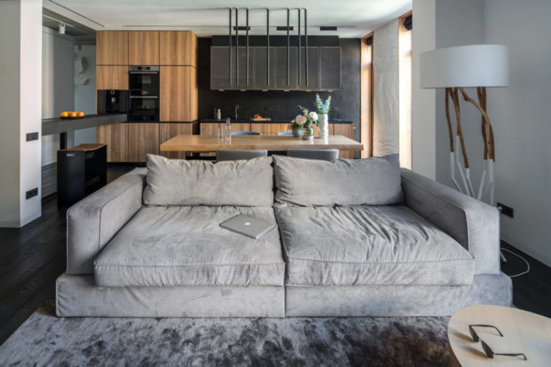 The large sofa serves a natural space divider, which separates but not too much