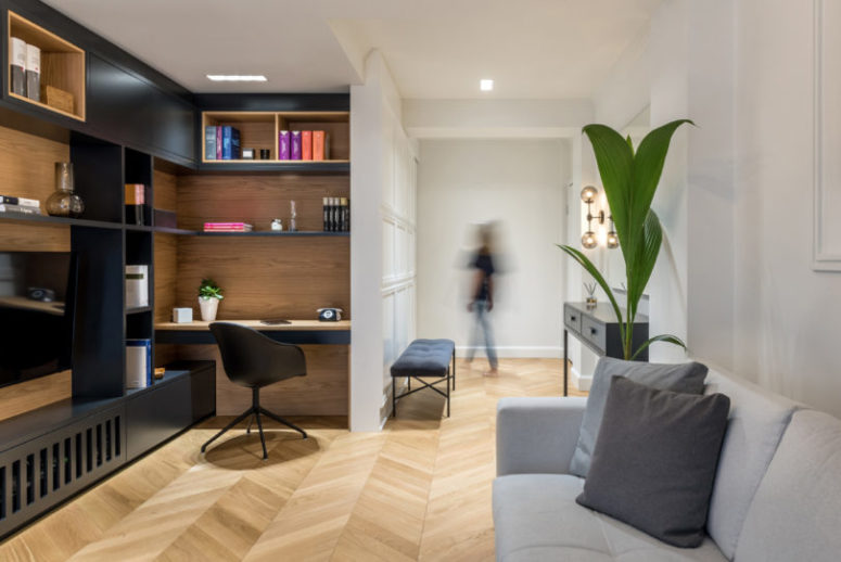 The living room features rather dramatic contrasts between black and wood and a comfy working space built-in